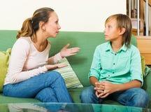 严肃的母亲和青少年的男孩谈话在家 免版税库存照片