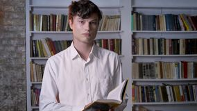 严肃的深色的人是阅读书,观看在照相机,背景的图书馆 股票视频