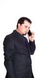 严肃的电话的商人 免版税库存照片