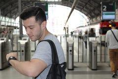 严肃的男性在检查在火车站的时间以后 免版税图库摄影