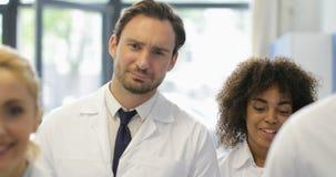 严肃的男性科学家步行在有混合种族研究员队的实验室谈论实验在现代实验室 影视素材