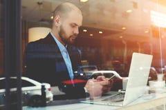 严肃的男性CEO在电视电话会议以后休息通过便携式计算机在他的商务旅行期间海外 免版税库存图片