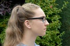 严肃的看的女孩,边面孔画象 免版税图库摄影