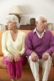 严肃的看起来的资深夫妇在家坐沙发 免版税库存照片