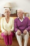 严肃的看起来的资深夫妇在家坐沙发 免版税库存图片