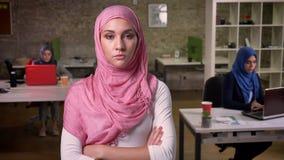 严肃的确信的好阿拉伯女性在手边站立用手在桃红色逗人喜爱的hijab,坐的回教女孩并且工作  股票视频