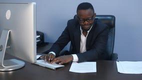 年轻严肃的美国黑人的商人画象与膝上型计算机和文件一起使用 免版税库存照片
