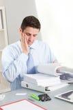 严肃的英俊的雇员读书指南 免版税库存照片