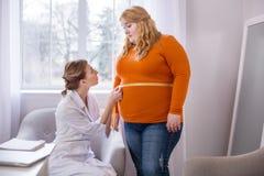严肃的营养师谈话与一名肥满妇女 库存图片