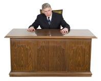 严肃的被隔绝的商人坐的企业书桌 免版税库存图片
