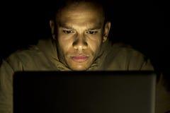 严肃的集中的人,在后他的膝上型计算机在晚上 免版税库存图片