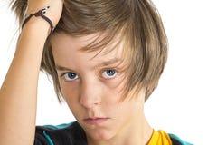 严肃的青少年的男孩,在他的头发的一只手,隔绝在白色 库存图片
