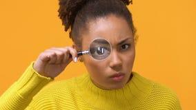 严肃的非洲妇女看通过放大镜的,女性探员,查寻 影视素材