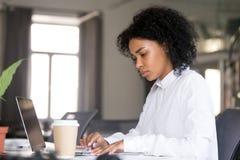 严肃的非裔美国人的妇女与文件一起使用在workpla 库存图片