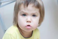 严肃的面孔女婴画象谈话与逗人喜爱的甜面颊 免版税库存图片