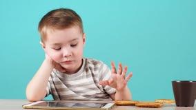 严肃的面孔逗人喜爱的小孩的关闭使用一平板电脑在桌,被隔绝坐蓝色 股票录像