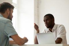 严肃的黑人工作者谈话与白种人同事在busin期间 免版税库存照片