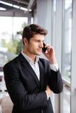 严肃的年轻商人谈话在手机在办公室 库存图片