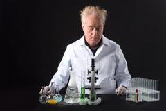 严肃的临床工作者在实验室和看学习烧瓶和泡影 免版税图库摄影