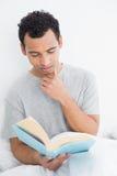 严肃的轻松的人阅读书在床上 库存照片