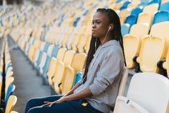 严肃的年轻美国黑人的女孩的特写镜头画象观察比赛,当坐体育场的位子时 库存照片