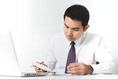 严重工作在有膝上型计算机的co办公室的亚洲商人 库存图片