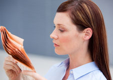 严重的女实业家读取报纸 免版税库存照片