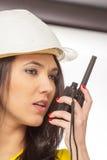 严重的女性建筑工人联系与携带无线电话 库存图片