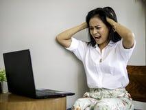 严重看在工作的繁忙的亚裔女商人问题计算机,她有在拿着头用有头疼的手的想法 免版税库存照片