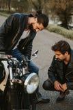 严重看在路的摩托车的两个男性朋友 库存照片