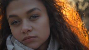 严重观看和直接地入在晴朗秋季的照相机的相当卷发的白种人女孩特写镜头画象  库存图片