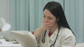 严重观看她的患者的结果的测试女性医生诊断疾病 免版税库存照片