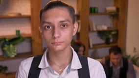 严重观看直接地入与他的家庭的照相机的少年阿拉伯男孩特写镜头画象在背景 影视素材