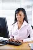 严重黑色女实业家的服务台 免版税库存照片