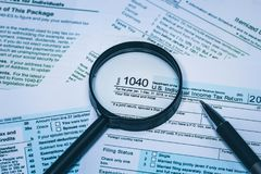 1040个个体与笔的收入税单详细的关闭的形式和放大镜个人单独财务的概念 免版税库存图片