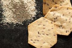 整个五谷有机薄脆饼干和面粉在黑色 库存图片