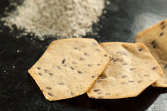 整个五谷有机薄脆饼干和面粉在黑色 免版税库存图片