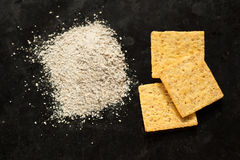 整个五谷有机面粉和黄色薄脆饼干堆在黑色 库存照片