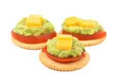 整个五谷薄脆饼干用蕃茄、鳄梨调味酱捣碎的鳄梨酱和乳酪 免版税图库摄影