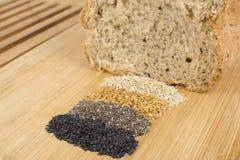 整个五谷面包谷物在木背景侧视图的 免版税库存图片