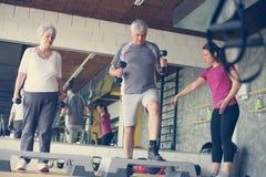 个人与资深夫妇的教练员运作的锻炼 免版税库存照片