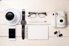个人办公室辅助部件、膝上型计算机、笔记本、咖啡杯和照相机平的位置在木背景,顶视图 免版税库存照片
