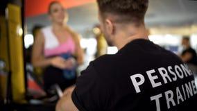 个人教练员谈话与女性健身房客户在锻炼,体育俱乐部服务以后 库存照片