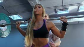 个人有举重的教练员帮助的妇女在健身房 库存照片