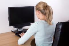个人计算机使用在办公室的后面的观点的妇女 免版税库存照片