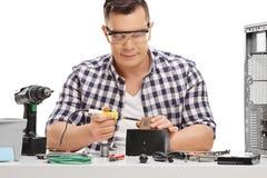 个人计算机技术员与焊铁一起使用 免版税库存图片