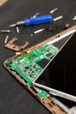 个人计算机片剂设备修理的过程在螺丝刀附近和咬住在黑木背景 拆卸 残破的玻璃,屏幕毁坏 免版税库存照片