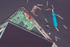 个人计算机片剂设备修理的过程在螺丝刀附近和咬住在黑木背景 拆卸 残破的玻璃,屏幕毁坏 库存图片