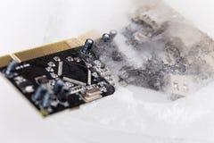 个人计算机的冻结的electonics委员会在冰 免版税图库摄影