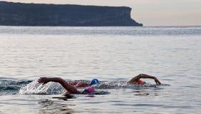 3个人采取海洋游泳 免版税库存照片